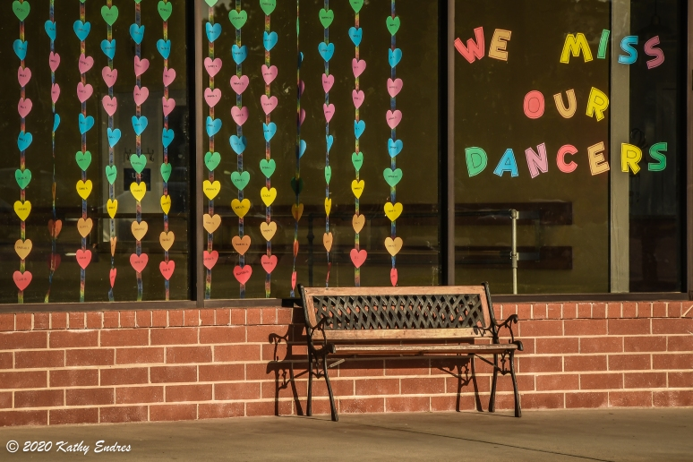 Many of us missed attending our group activities when states locked down. This storefront message shows how instructors likewise missed seeing their dancers, who were each represented by a colored heart. The feeling of melancholy is also characterized by the empty bench in this photo.